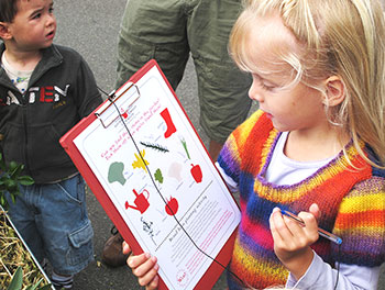 Young female student holding a clipboard containing a worksheet about food education.