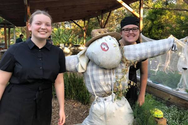 Two young people either side of a scarecrow